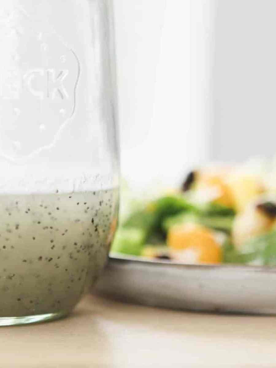 A bottle sits on the table top filled with homemade poppy seed dressing. Beside it sits a vibrant salad on a plate.