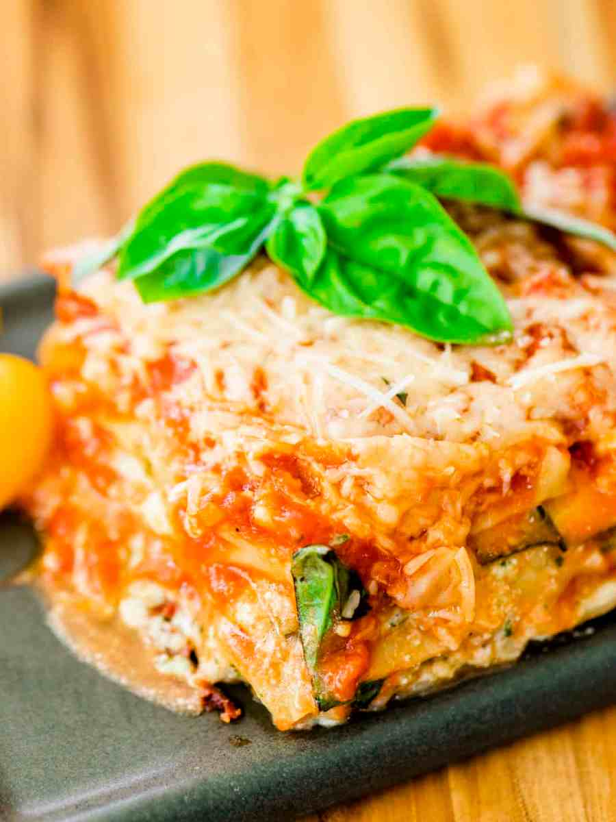 Slice of zucchini and pesto lasagna sits on a plate ready to eat. It is garnished with fresh basil leaves.