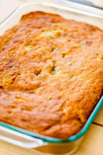 Fresh banana cake sits in a glass 9x13 dish, un-iced and golden brown.