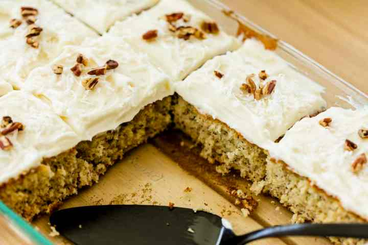 Fresh Banana Cake garnished with Coconut Cream Cheese frosting, shredded coconut and pecans, sits in a 9x13 dish.