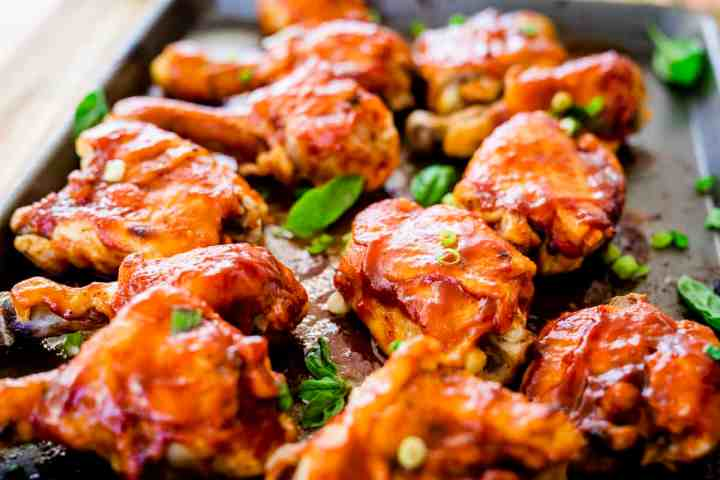 Juicy barbecue chicken sits on a pan. Thighs and drumsticks are generously coated with barbecue sauce.