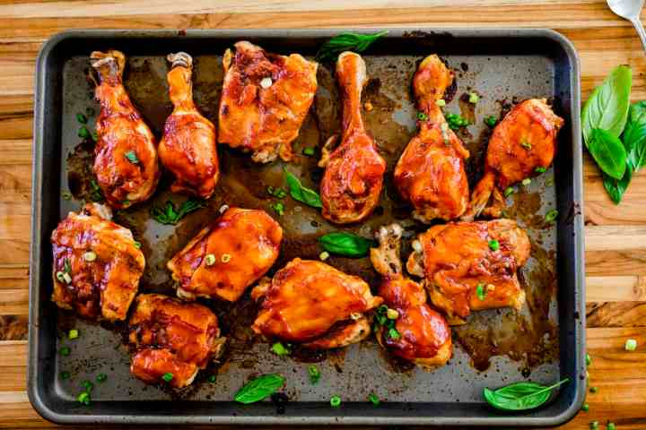 Delicious drumsticks and thighs sit on a baking sheet covered in caramelized barbecue sauce, ready to enjoy.