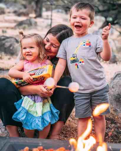 Ashley, James and George sit behind a campfire smiling and laughing while making smores.