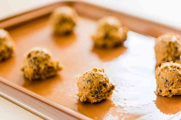 Scooped balls of cookie dough are sitting on a greased cookie sheet.