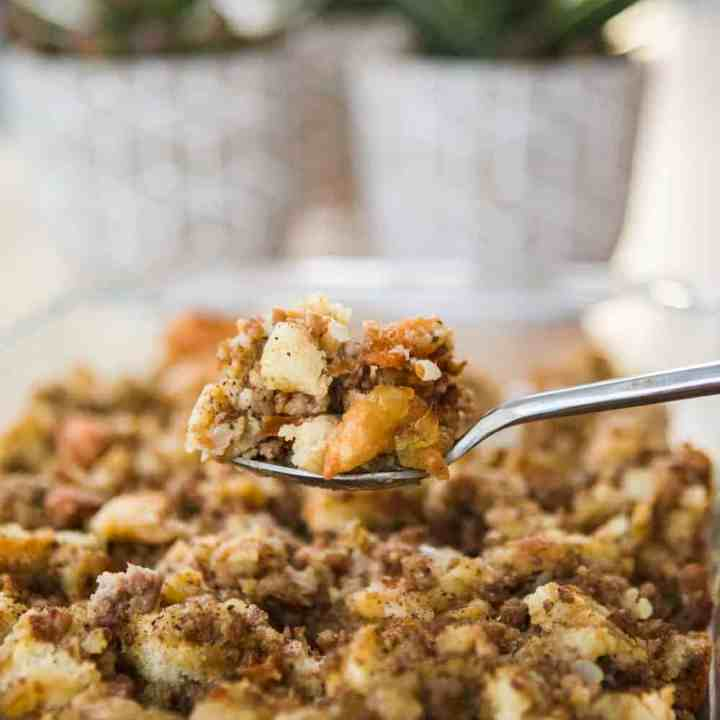 Spoonful of hearty sausage stuffing sits over a baked casserole dish.
