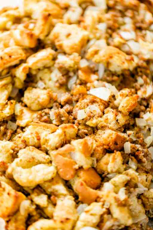 Closeup of freshly cooked sausage stuffing sits in a casserole dish ready to enjoy.