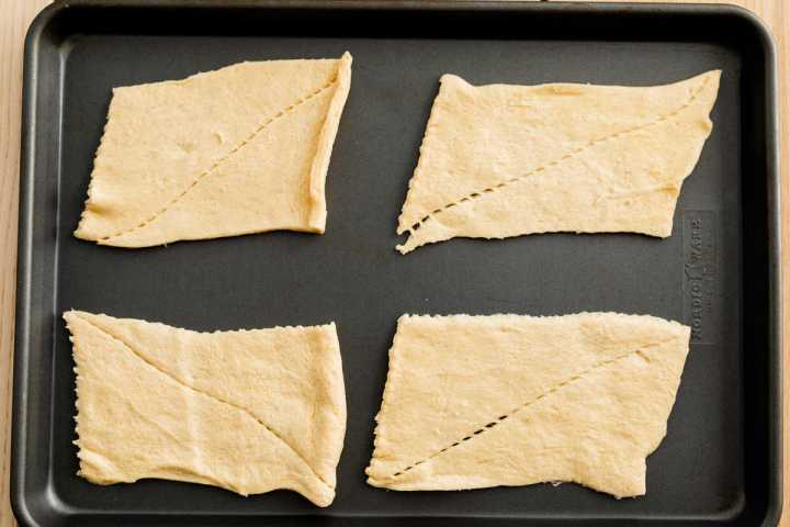 Crescent roll dough has been unrolled and separated into four rectangular sections.
