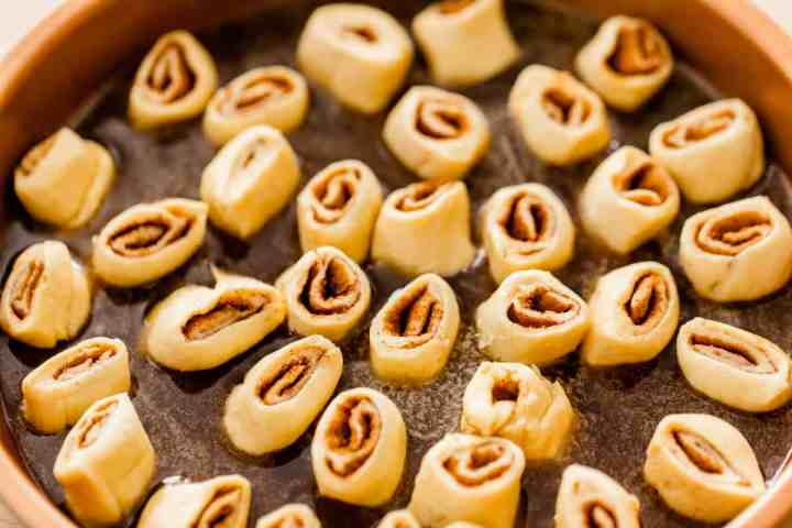 Each mini cinnamon roll sits in the syrup filled pie dish ready to bake.
