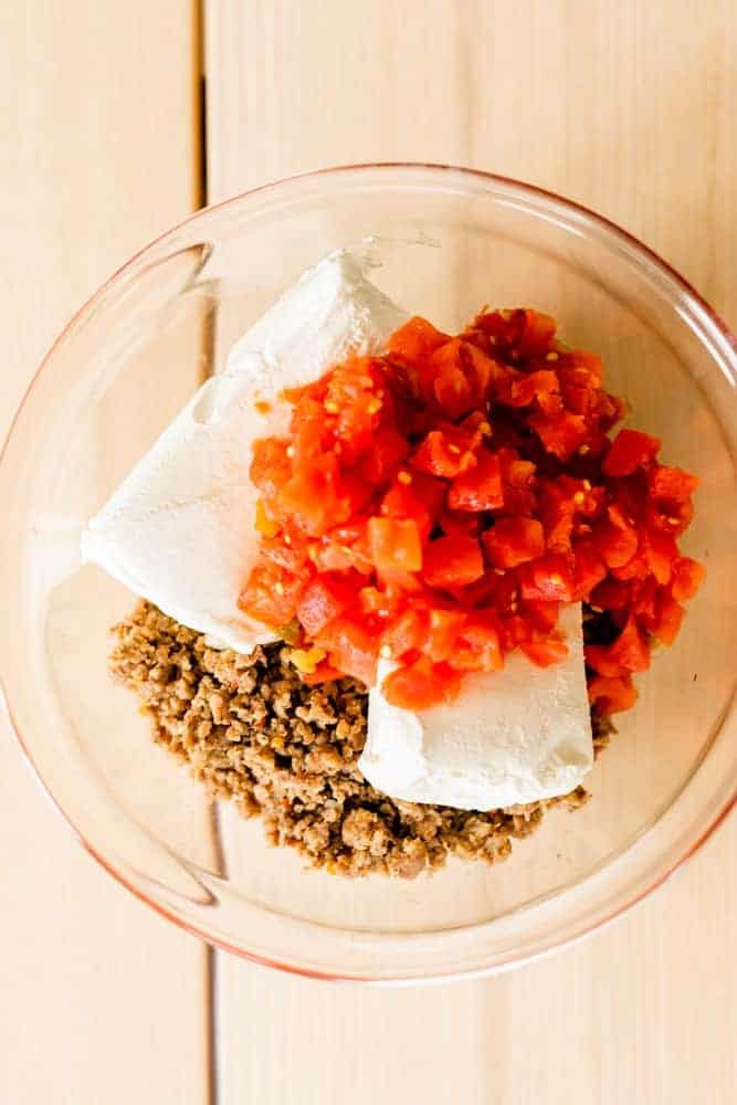 A glass bowl is filled with crumbled hot sausage, two blocks of cream cheese and a can of Rotel.