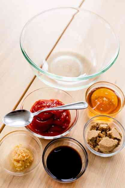 All ingredients for the honey garlic sauce sit on the table beside a large glass bowl.