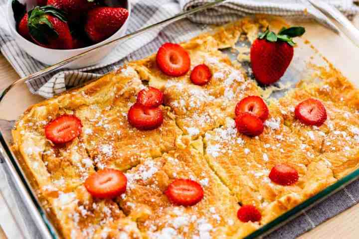 German Pancakes sit in casserole dish, sliced and topped with strawberries and powdered sugar to serve.