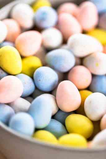 A ceramic bowl is filled with Cadbury Mini Eggs. Eggs are light pastel colors, blue, pink, yellow and white.