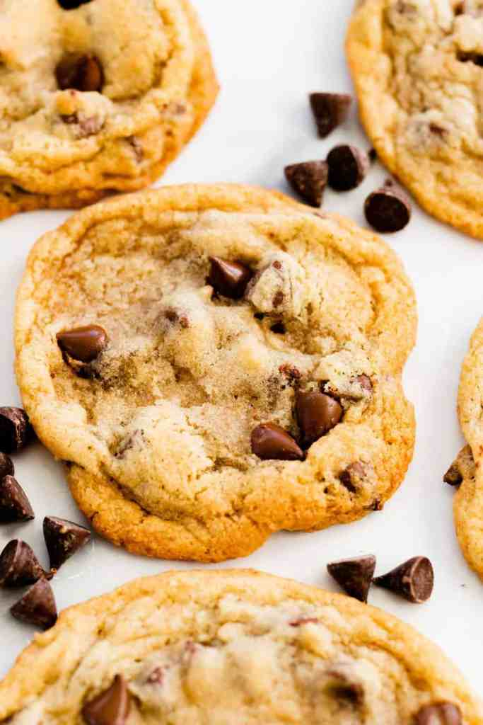 A big fresh, chocolate chip cookie sits on the counter top surrounded by other cookies and scattered chocolate chips.