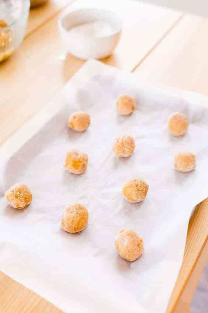 Cookie dough balls sit on a baking sheet covered with parchment paper, ready to go in the oven.