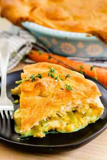 A slice of Chicken Pot Pie sits on a plate alongside a fork, ready to be enjoyed.