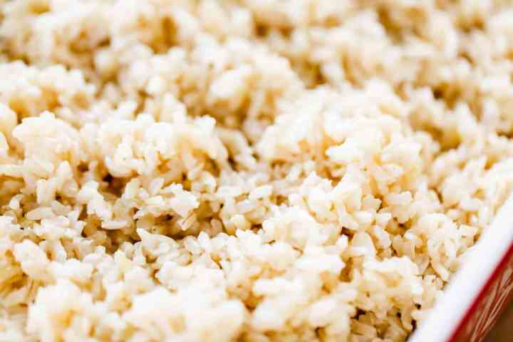 Fluffy baked brown rice sits in a ceramic casserole dish ready to serve.