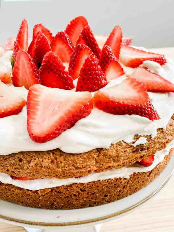 Freshed sliced strawberries decorate the top of a 2 layered cake.