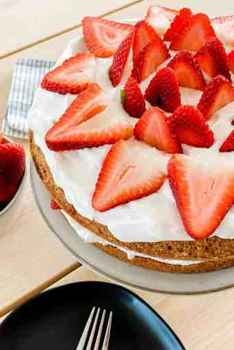 On a counter sits a cake stand topped with strawberry cake and whipped cream.