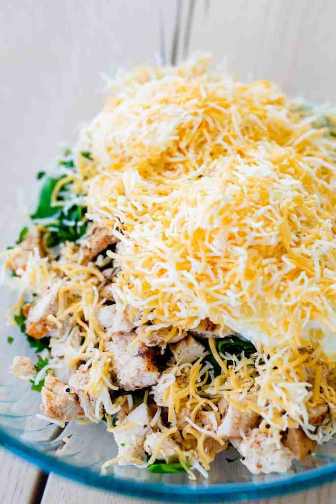 Shredded cheese sits on top of other ingredients in a large glass bowl.