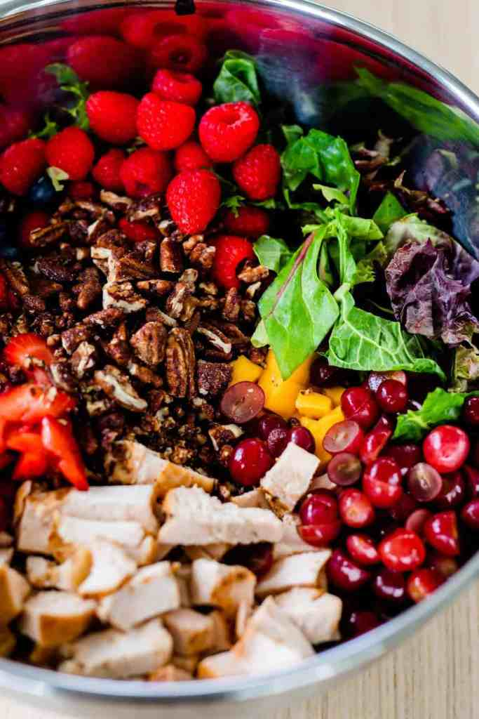 Candied walnuts have been added to a large metal bowl sits on the countertop filled with mixed greens, grilled chicken, vibrant berries and mango.