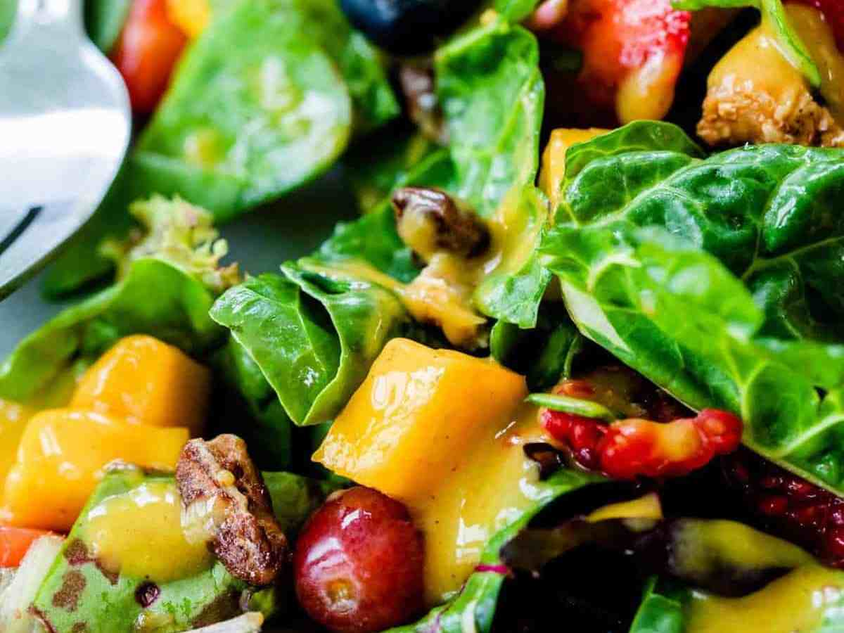 A serving of Mango Berry Salad on a plate, drizzled with creamy Cinnamon Mango Dressing, ready to eat!