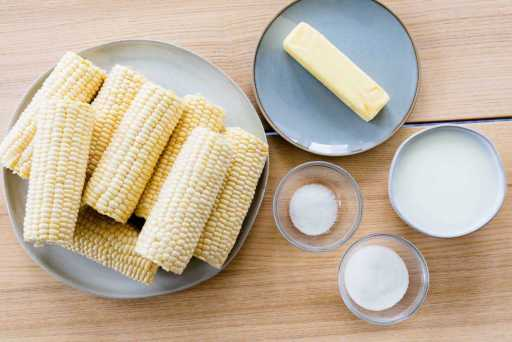 Ingredients for corn on the cob sit on counter, Husked corn, stick of butter, salt, sugar and milk.