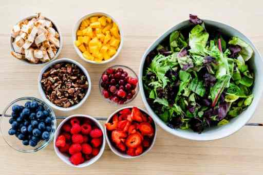 Blueberries, Raspberries, Strawberries, Grapes, Mangoes, Mixed Greens, Grilled Chicken sit in individual bowls on a table top ready to be combined.