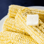 A stack of corn sits on a plate ready to eat and enjoy.