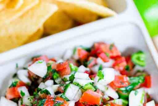 Chilled Pico de Gallo sits in a white ceramic serving dish alongside crispy corn tortilla chips.