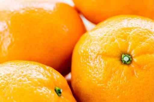 A glass bowl is filled with bright clementine oranges.