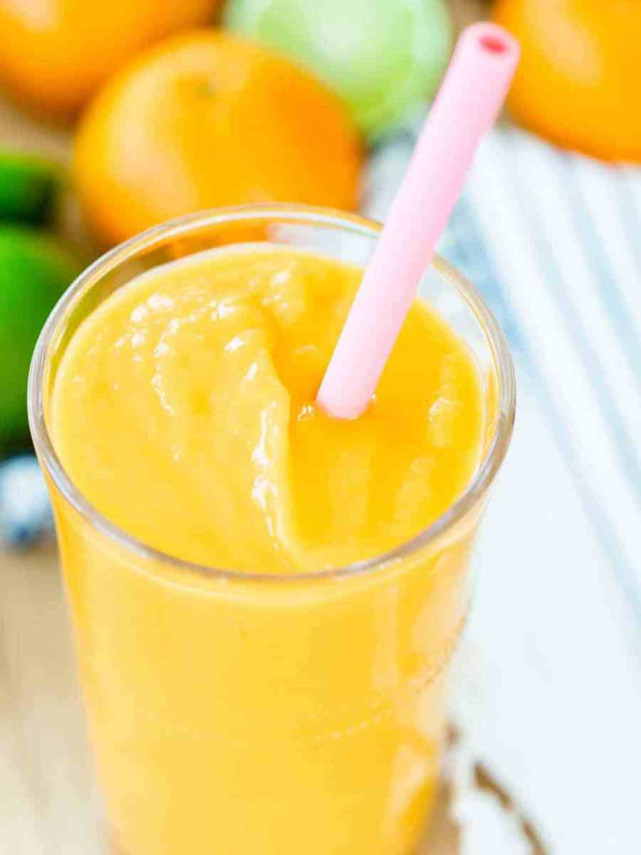 A tall glass of Orange Mango smoothie sits in front of oranges and limes. A pink straw sits in the glass.