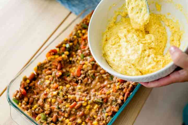 Cornbread mixture in bowl is held over the casserole dish and ready to be added to tamale pie.