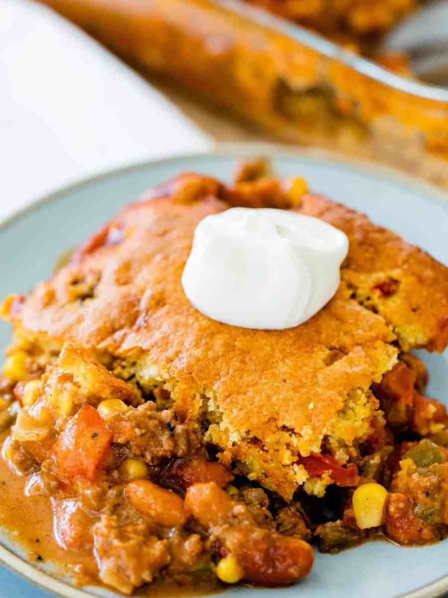 Serving of tamale casserole sits on a plate ready to eat, garnished with sour cream.