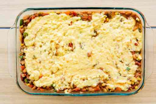 An unbaked pan of tamale pie is topped with cornbread mix, ready to bake.