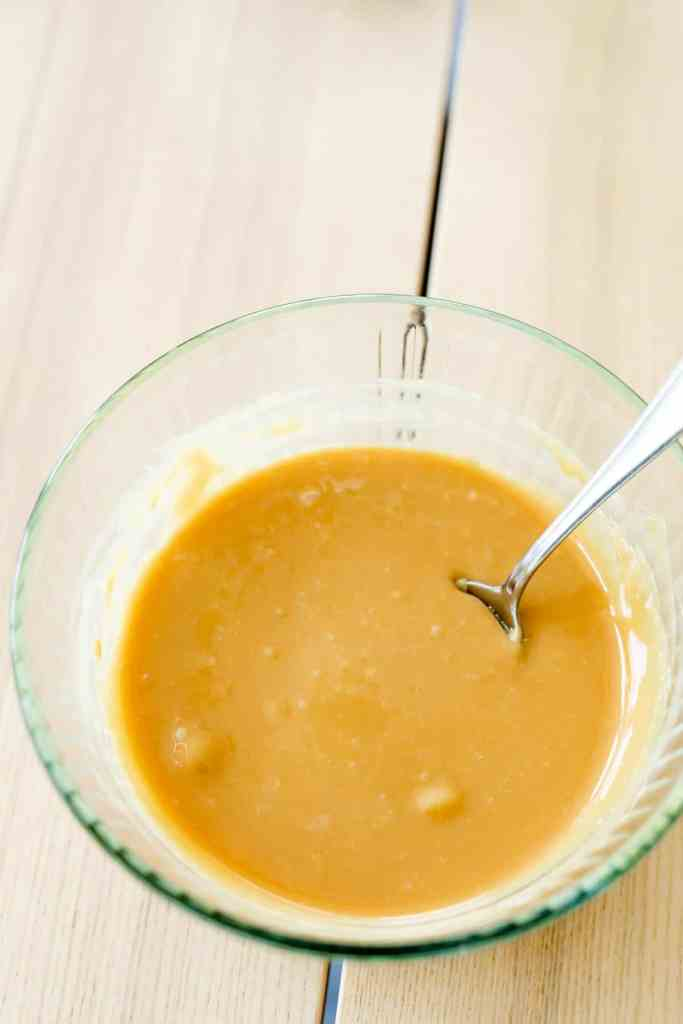 Melted caramel sauce sits in a glass bowl with a spoon.