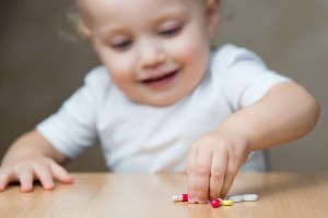 A toddler picks up medication pills from a tabletop.