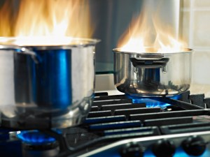 Fire shoots from two pans left unattended on a stovetop.