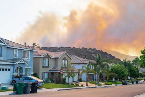 Wildfire burning behind houses
