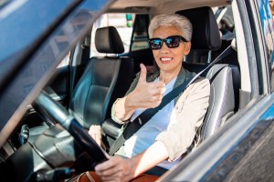 A smiling older woman gives a thumbs-up while wearing a seat belt.