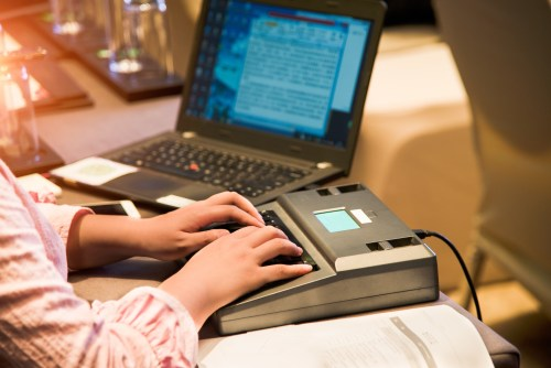 A court reporter uses a high-technology stenography machine.