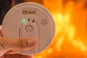 A carbon monoxide alarm near a fireplace.
