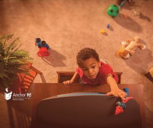A small boy climbs up a cabinet to reach a toy on top of a TV.