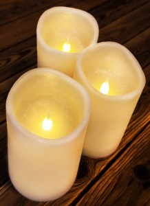 Flameless candles glow on a wood table.