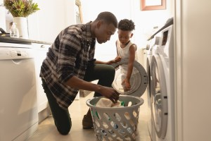 A father and his son gather laundry from the dryer.