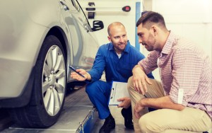 A mechanic points to a tire with the car's owner looking on.