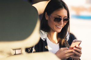A smiling woman enters information into her phone while sitting in a car's backseat with the door open.