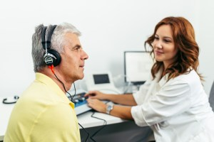 An audiologist adjust dials while giving an older man a hearing test.