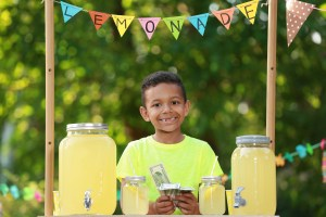A boy at a lemonade stand counts his earnings.