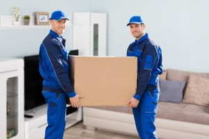 Two uniformed moving men carry a heavy box.