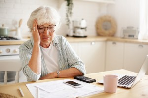 An older woman worries over bills spread on a table in front of her.